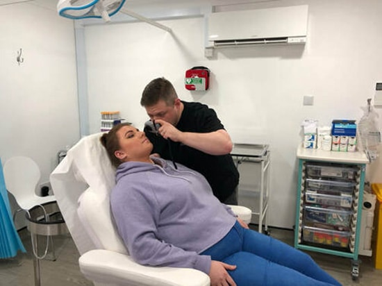 Dr Kieron McDaid performing a mole removal consultation